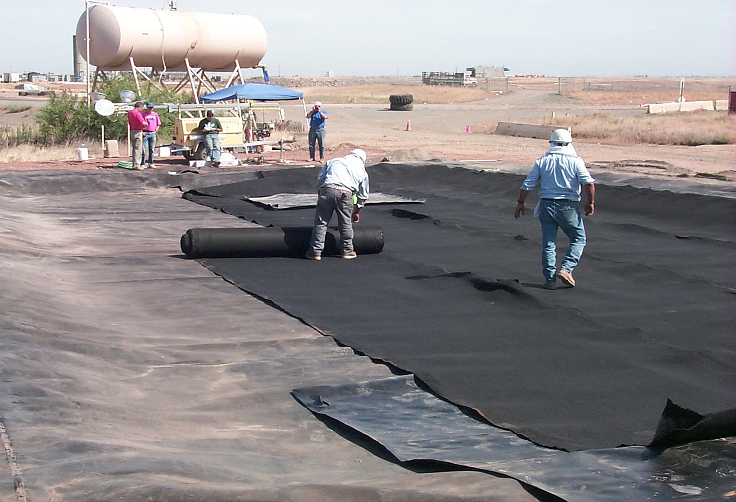 Installation of a geomembrane and overlying drainage layer for a composite liner. Photo by Bill Albright.